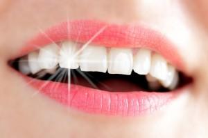 Frauenlachen mit Lichtreflex auf Zahn dank professioneller Zahnreinigung